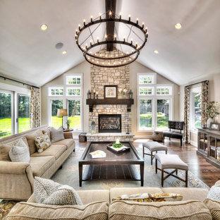 Imagen de salón para visitas abierto, tradicional, extra grande, con paredes beige, suelo de madera en tonos medios, chimenea tradicional y marco de chimenea de piedra