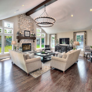 Huge transitional open concept medium tone wood floor living room photo in Kansas City with beige walls, a standard fireplace, a stone fireplace and a wall-mounted tv