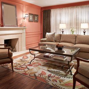 Modelo de salón para visitas cerrado, clásico, de tamaño medio, sin televisor, con paredes rosas, suelo de madera oscura, chimenea tradicional, marco de chimenea de piedra y suelo marrón