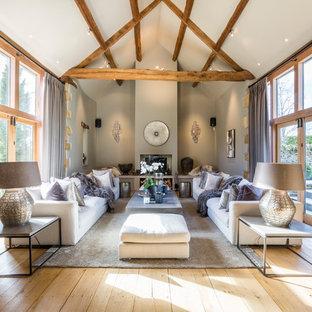 Foto de salón para visitas abierto, campestre, de tamaño medio, con paredes grises, suelo de madera clara, estufa de leña y suelo beige