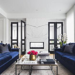 На фото: парадная гостиная комната в современном стиле с белыми стенами, паркетным полом среднего тона, двусторонним камином, фасадом камина из камня и желтым полом