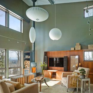 Esempio di un soggiorno contemporaneo con sala formale, TV a parete, pareti verdi e stufa a legna