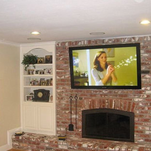 Imagen de salón grande con paredes beige, moqueta, chimenea tradicional, marco de chimenea de ladrillo y televisor colgado en la pared