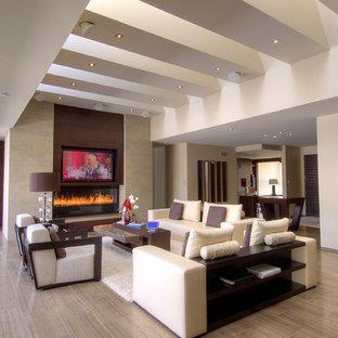 トロントの大きいコンテンポラリースタイルのおしゃれなLDK (ベージュの壁、磁器タイルの床、横長型暖炉、石材の暖炉まわり、埋込式メディアウォール、茶色い床、フォーマル) の写真