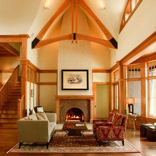 Ispirazione per un soggiorno american style aperto con sala formale, pareti beige, pavimento in legno massello medio, camino classico, cornice del camino in mattoni e pavimento arancione