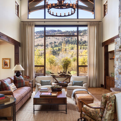 Example of a large mountain style formal and open concept medium tone wood floor and brown floor living room design in Other with beige walls, a standard fireplace and a stone fireplace