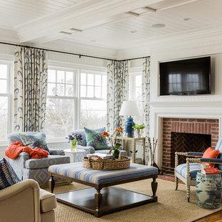 На фото: гостиная комната в викторианском стиле с белыми стенами, темным паркетным полом, стандартным камином, фасадом камина из кирпича и телевизором на стене с