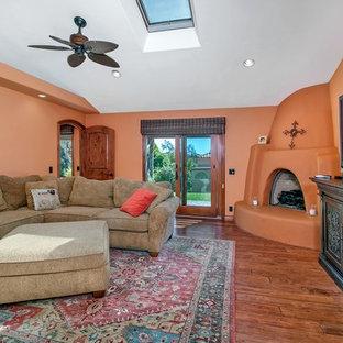 サンディエゴの大きいサンタフェスタイルのおしゃれな独立型リビング (オレンジの壁、濃色無垢フローリング、コーナー設置型暖炉、漆喰の暖炉まわり、据え置き型テレビ、茶色い床) の写真