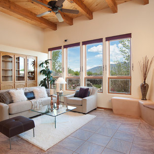 Example of a large southwest formal and open concept porcelain floor living room design in Albuquerque with white walls, a standard fireplace, a plaster fireplace and a media wall