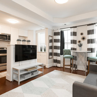 Photo of a classic living room in DC Metro with white walls, dark hardwood flooring and a wall mounted tv.