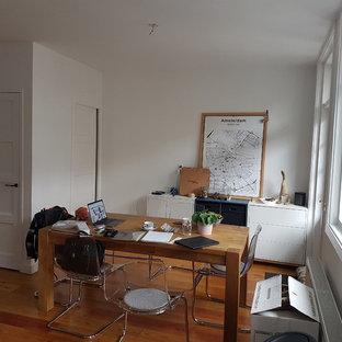 Foto di un piccolo soggiorno minimalista stile loft con pareti grigie, pavimento in compensato, cornice del camino in pietra e TV a parete
