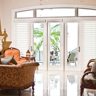 Immagine di un soggiorno tropicale di medie dimensioni e chiuso con sala formale, pareti beige, pavimento in gres porcellanato, camino classico e cornice del camino in intonaco