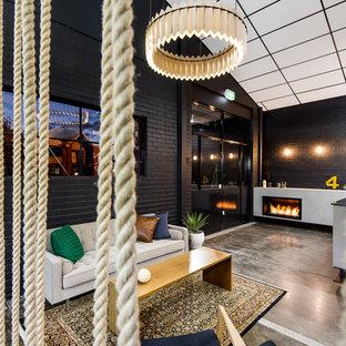 パースの中サイズのインダストリアルスタイルのおしゃれなLDK (黒い壁、コンクリートの床、標準型暖炉、コンクリートの暖炉まわり) の写真