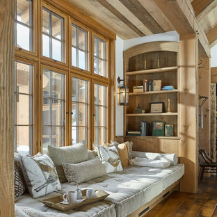 Immagine di un soggiorno stile rurale con pareti bianche, pavimento in legno massello medio e pavimento marrone