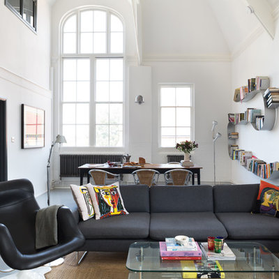 Urban open concept concrete floor living room library photo in London with white walls and no fireplace