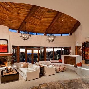 Cette image montre un salon sud-ouest américain ouvert avec un mur blanc, moquette, une cheminée standard, un manteau de cheminée en pierre et un sol beige.