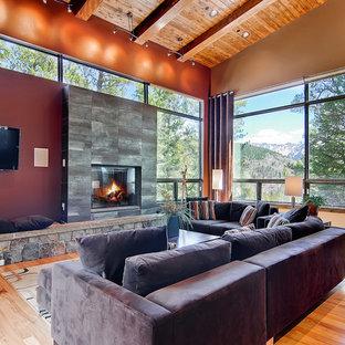 Foto di un soggiorno design con pareti rosse, pavimento in legno massello medio, camino classico e TV a parete