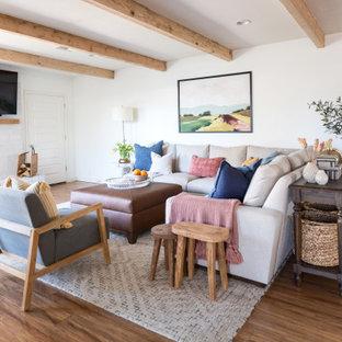 Ejemplo de salón abierto, campestre, de tamaño medio, con paredes blancas, suelo laminado, chimenea tradicional, marco de chimenea de ladrillo, televisor colgado en la pared y suelo marrón