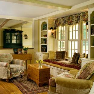 Esempio di un grande soggiorno country aperto con pareti gialle, pavimento in legno massello medio e libreria