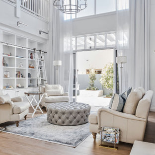 Design ideas for a beach style open concept living room in Gold Coast - Tweed with white walls, medium hardwood floors and brown floor.