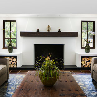 This is an example of a large traditional formal open concept living room in Santa Barbara with white walls, terra-cotta floors, a standard fireplace, a plaster fireplace surround and red floor.