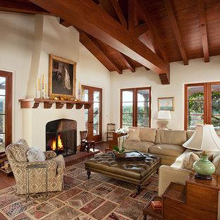サンタバーバラの大きい地中海スタイルのおしゃれなLDK (フォーマル、白い壁、濃色無垢フローリング、標準型暖炉、漆喰の暖炉まわり、壁掛け型テレビ) の写真