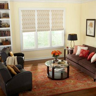 Idee per un grande soggiorno classico aperto con libreria, pareti gialle, parquet scuro, nessun camino e pavimento marrone