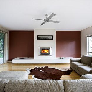 Foto på ett stort funkis allrum med öppen planlösning, med ett finrum, röda väggar, bambugolv, en standard öppen spis och en spiselkrans i gips