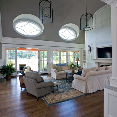 Inspiration for a large timeless formal and open concept medium tone wood floor living room remodel in Baltimore with gray walls, a standard fireplace, a plaster fireplace and a wall-mounted tv
