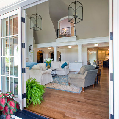 Inspiration for a large timeless formal and open concept medium tone wood floor living room remodel in Baltimore with gray walls and a wall-mounted tv