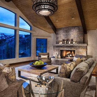 Idee per un grande soggiorno minimal stile loft con pareti beige, pavimento in legno massello medio, camino classico, cornice del camino in pietra e nessuna TV