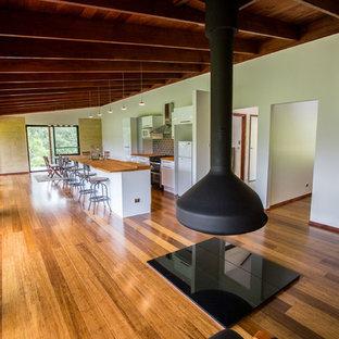 Ispirazione per un piccolo soggiorno design aperto con pareti bianche, pavimento in bambù, camino sospeso e nessuna TV