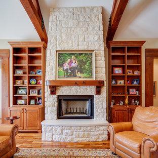 Imagen de salón para visitas abierto, rural, grande, sin televisor, con suelo de madera en tonos medios, chimenea tradicional, marco de chimenea de piedra y paredes beige