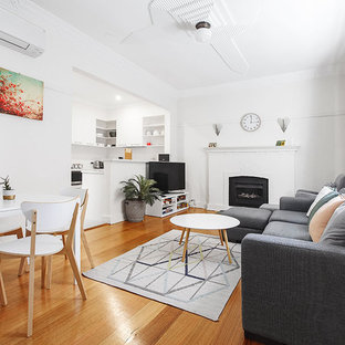 Photo of a small contemporary enclosed living room in Melbourne with white walls, medium hardwood floors, a standard fireplace, a concrete fireplace surround, a freestanding tv and brown floor.