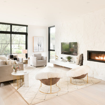 Living room - scandinavian open concept light wood floor and beige floor living room idea in Toronto with white walls, a ribbon fireplace, a stone fireplace and a wall-mounted tv