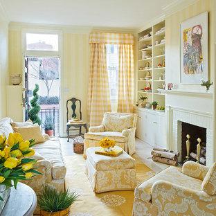 Idee per un soggiorno classico con pareti gialle, camino classico e cornice del camino in mattoni