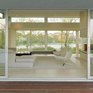Esempio di un soggiorno minimal con camino bifacciale e pavimento beige