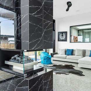Foto di un grande soggiorno aperto con pareti beige, pavimento in pietra calcarea, camino sospeso, cornice del camino in pietra e pavimento grigio