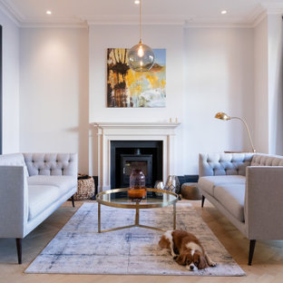 Inspiration for a medium sized contemporary open plan living room in London with a reading nook, white walls, light hardwood flooring, a standard fireplace, a plastered fireplace surround and beige floors.