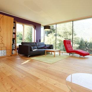 Ejemplo de salón actual, de tamaño medio, con paredes púrpuras, suelo de madera clara y estufa de leña