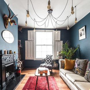 Ispirazione per un soggiorno boho chic di medie dimensioni e chiuso con pareti blu, camino classico, TV autoportante, pavimento marrone e pavimento in legno massello medio