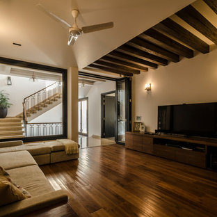 Imagen de sala de estar cerrada, de estilo zen, con paredes blancas, suelo de madera en tonos medios, televisor independiente y suelo marrón