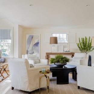 ボストンの中サイズのビーチスタイルのおしゃれなLDK (白い壁、淡色無垢フローリング、標準型暖炉、ベージュの床、フォーマル、コンクリートの暖炉まわり、テレビなし) の写真