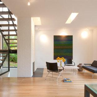 Idées déco pour un salon moderne avec un mur blanc, une cheminée standard, aucun téléviseur et un manteau de cheminée en brique.