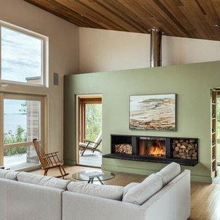 Imagen de salón abierto, rural, con paredes verdes, suelo de madera clara y estufa de leña