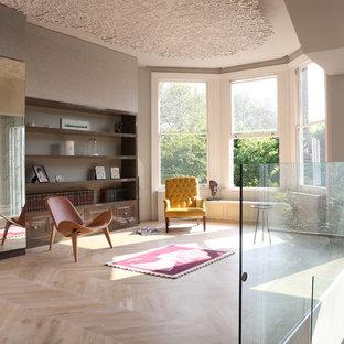 Foto de salón tipo loft, actual, con paredes grises y suelo de madera clara