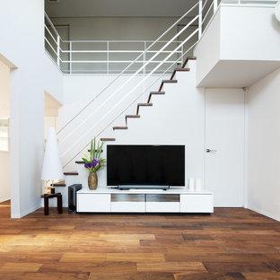 他の地域のモダンスタイルのおしゃれなリビング (据え置き型テレビ、グレーの壁、濃色無垢フローリング、茶色い床) の写真