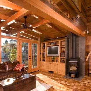 Imagen de salón abierto, rural, con marco de chimenea de piedra, estufa de leña, suelo de madera en tonos medios y televisor colgado en la pared