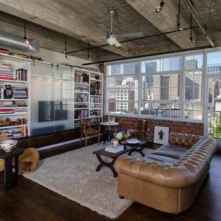 Immagine di un soggiorno industriale con libreria e TV nascosta
