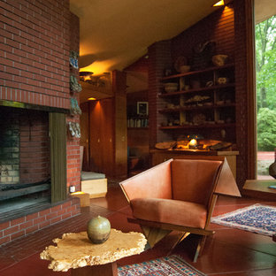 Living room - modern red floor living room idea in Cleveland with a standard fireplace and a brick fireplace